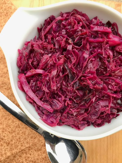 Braised red cabbage with cranberries and maple in a serving bowl with a serving spoon at the side.