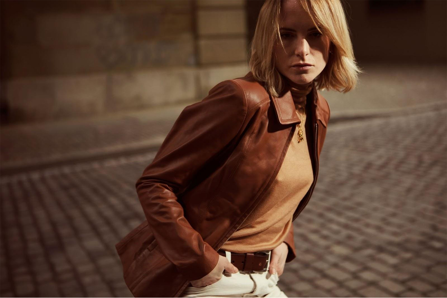 a stylish woman in a leather jacket is posing on the street at night.