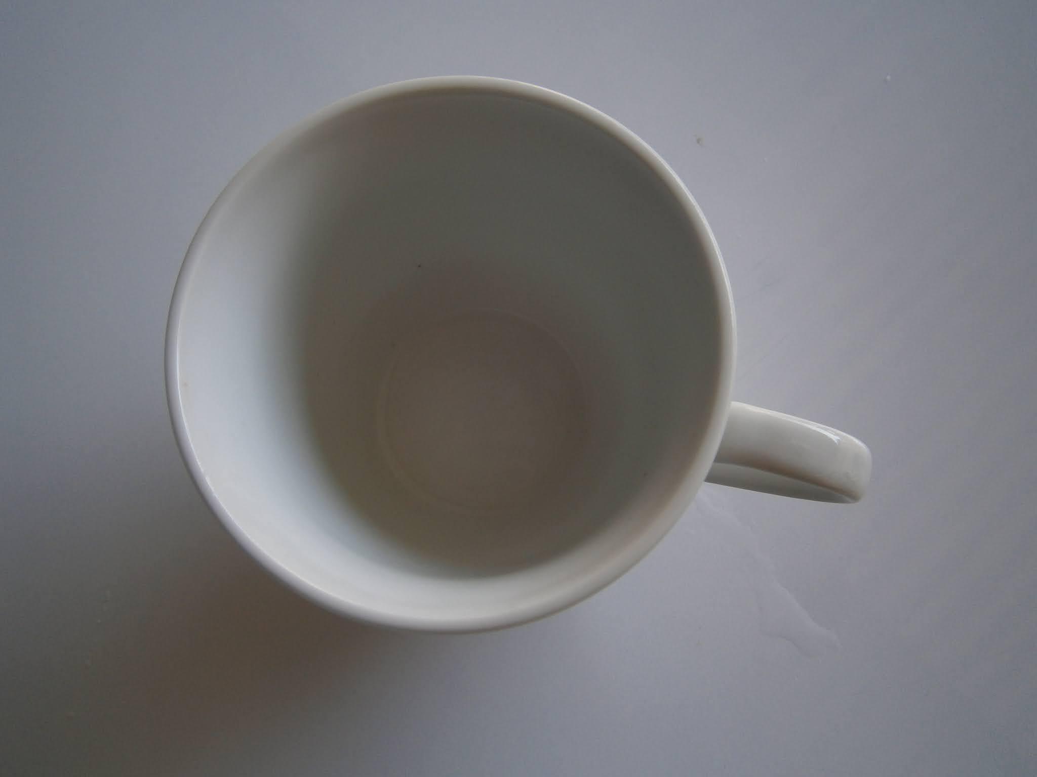 Taza de café puesto sobre un fondo de color blanco para decoración