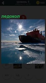Под ярким солнцем идет ледокол, ломает толстый лед, прокладывая путь