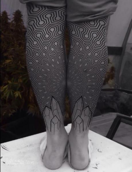 vemos una pierna con tatuajes geometricos