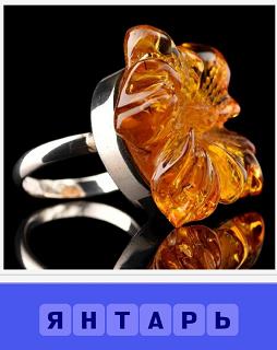 на столе лежит роскошный янтарь в обрамлении в кольце