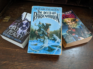 "Three books resting on a dark wooden surface. The books are all by Elizabeth Moon, in the Paksenarrion series. They are ""The Deed of Paksenarrion"", ""Oath of Fealty"", and ""The Legacy of Gird""."