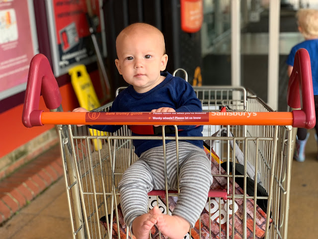 A baby boy in a Sainsburys shopping trolley about to go into the supermarket for a frugal family shop