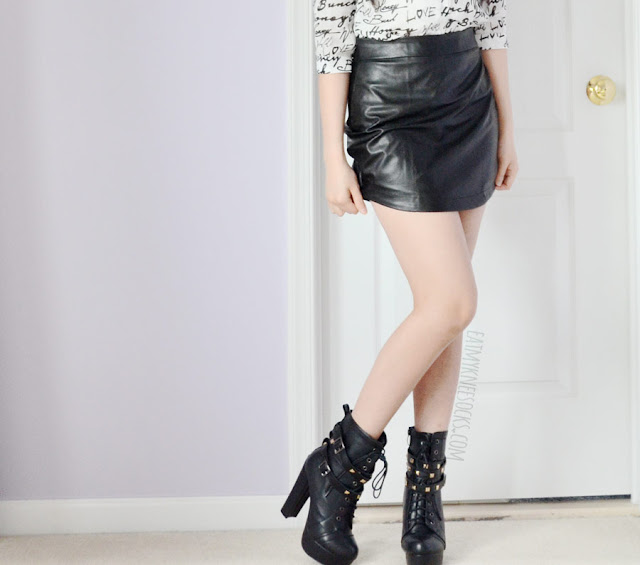 A sleek, edgy, modern outfit featuring Dresslink's black curved faux leather bodycon skirt, heeled platform lace-up boots, and a graffiti-print blouse.