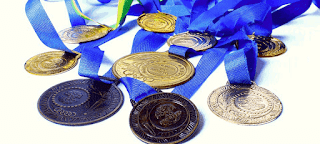 A variety of medals on blue ribbons lying in a pile, representing the concept of rewards, which is how many players perceive experience points.