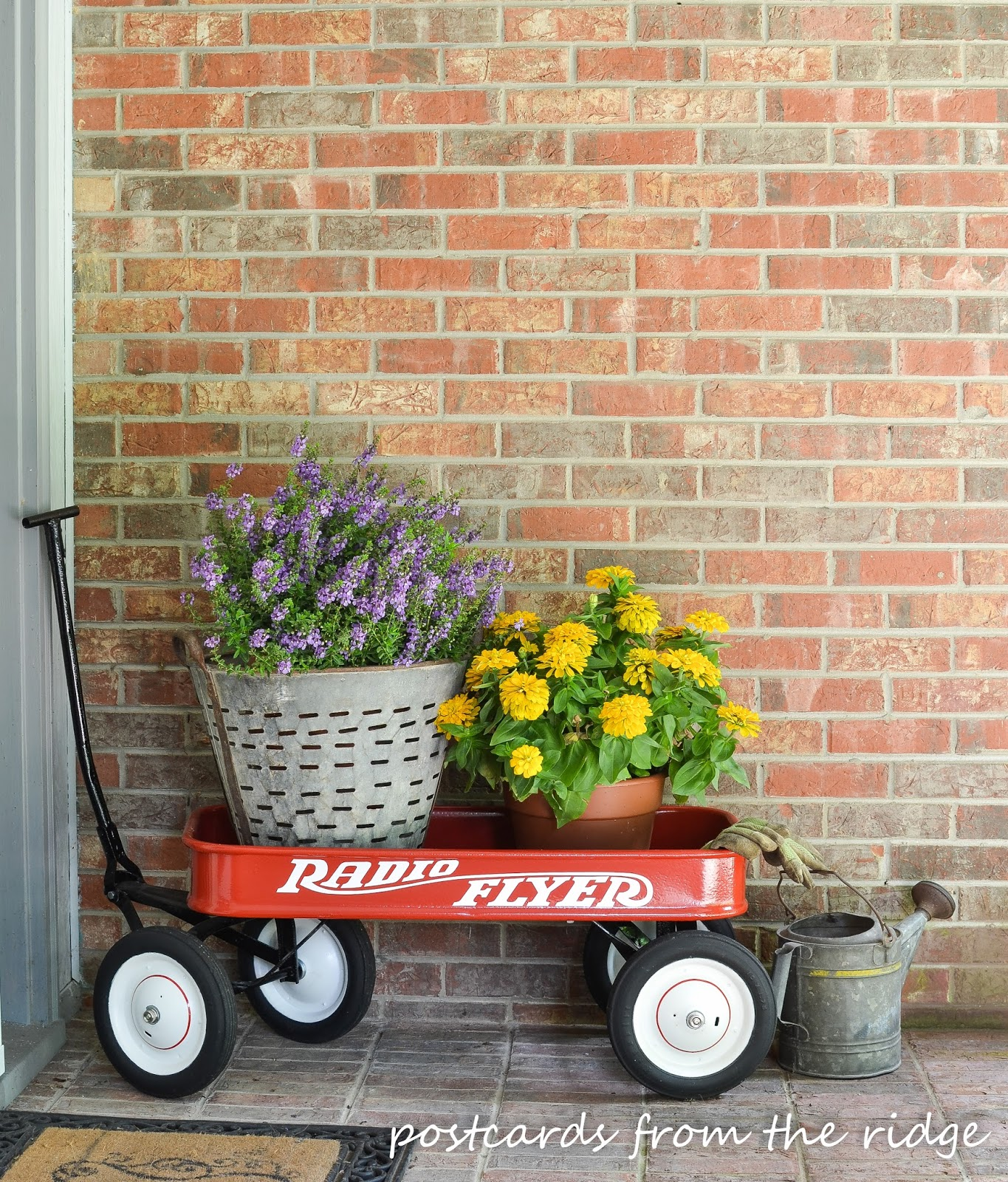 vintage red radio flyer wagon with summer flowers and vintage olive bucket