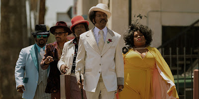 "Craig Robinson, Mike Epps, Tituss Burgess, Eddie Murphy, and Da'Vine Joy Randolph walk down the street in Netflix's ""Dolemite Is My Name."""