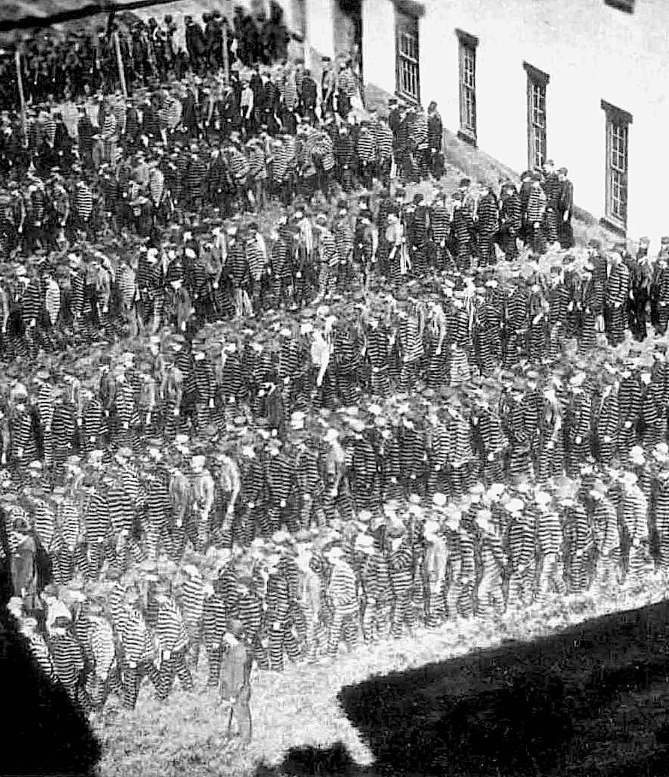 1890 uniformed prisoners move in a lockstep shuffle in this photograph