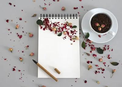 كراسة بيضاء فارغة وعليها قلم وبجانبها كوب قهوة وورود منثورة على المكتب