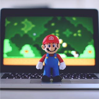 Nintendo Mario figure   standing by a laptop screen