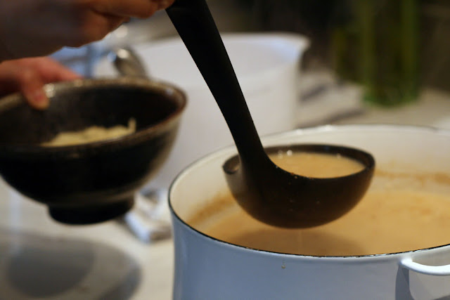 A ladle scooping some pork bone broth into a bowl of freshly cooked homemade ramen noodles.
