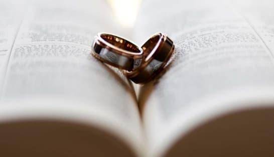 A imagem mostra duas alianças sobre uma bíblia aberta