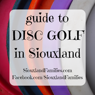 """in background, the bottoms of  five disc golf discs form graphic stripes. in foreground, the words """"guide to disc golf in Siouxland"""" and """"SiouxlandFamilies.com Facebook.com/SiouxlandFamilies"""""""