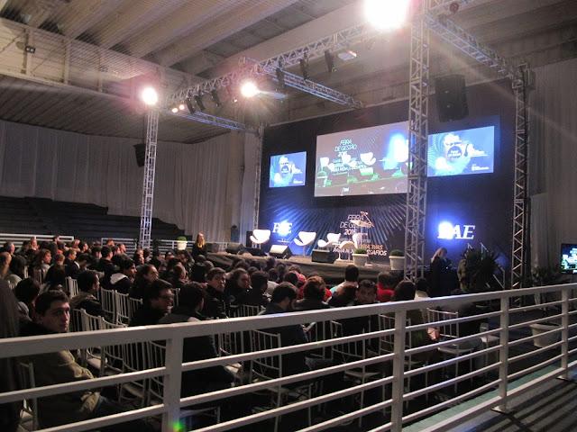 Imagem mostrando a imagem geral do local do evento. Em primeiro plano mostra o público e ao fundo o palco.