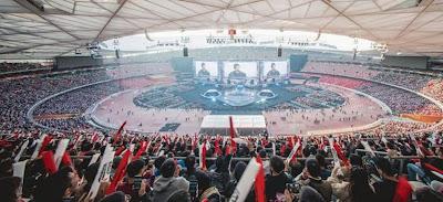 Estádio lotado vendo a final do mundial com três telões ao fundo.