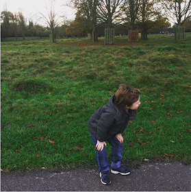 Boy in a coat in a park with a grey sky over head - Top five tips for helping autistic kids in wet weather