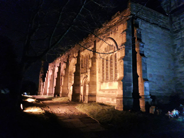 Image shows St Oswald's Church, Winwick, lit up at night