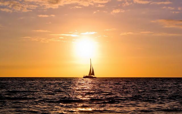Foto met een zeilboot bij zonsondergang