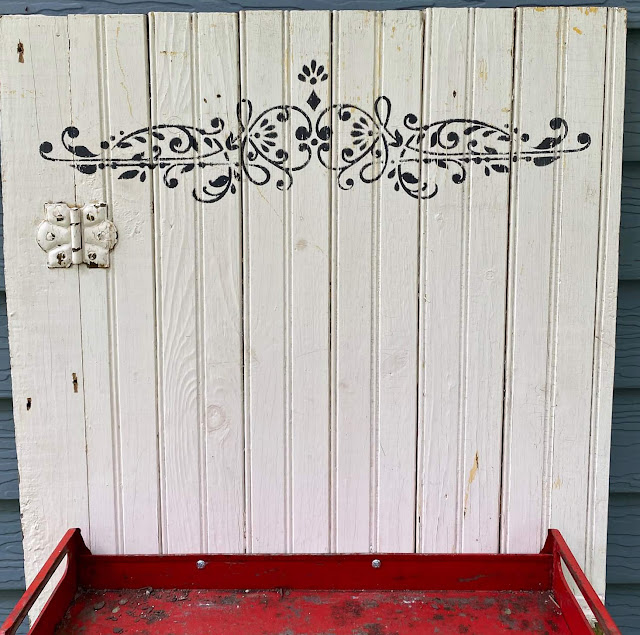 Photo of a scrolly stencil on an old beadboard cabinet door