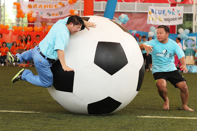 Huge Soccer Ball with 2 Men Trying to Play Soccer with It