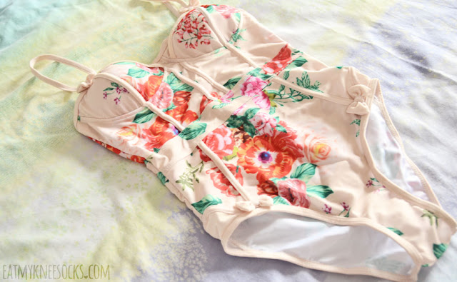 Details on the floral bow-accented contrast trim peach-beige one-piece swimsuit from Gamiss.