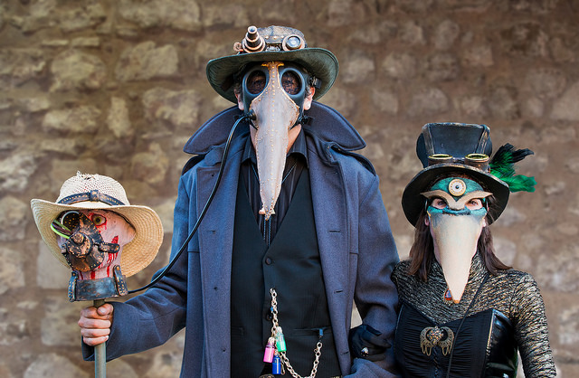 Steampunk couple dressed as plague doctors with leather bird masks