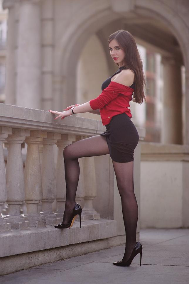 Czarna obcisła sukienka, czerwony cardigan i czarne rajstopy