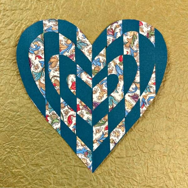 woven paper heart made of decorative papers displayed on gold textured paper