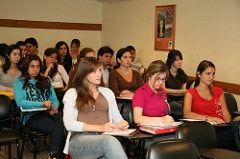 Clase de estudiantes en una carrera corta, sentados en un salón con sus cuadernos