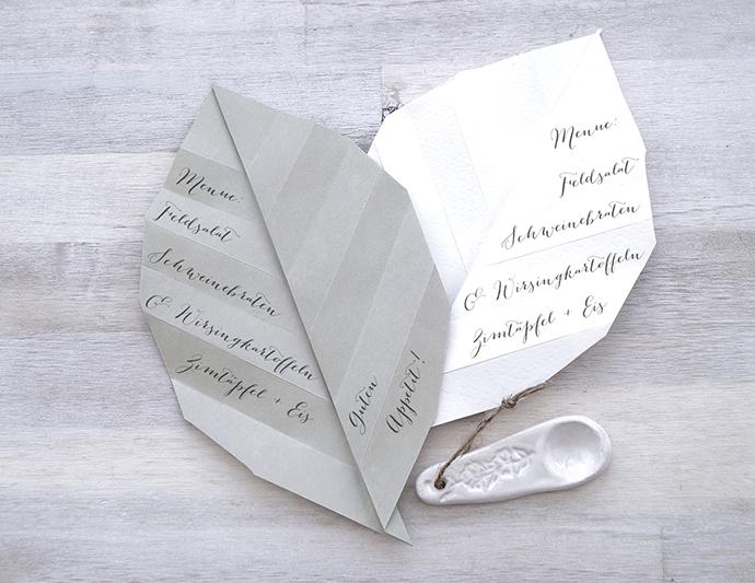 2 große Origamiblätter als Menükarte mit Text.