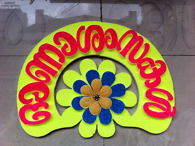 "This says ""Onaashamsagal"" or ""Onam Wishes""/""Happy Onam""."