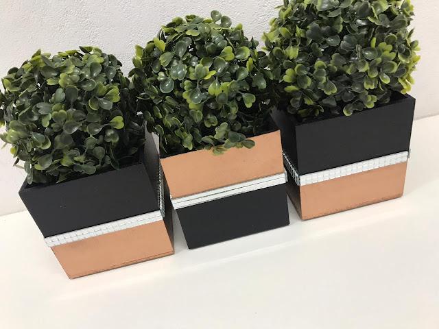 Três cachepots com pintura preto e cobre e plantinhas artificiais do tipo buxinho.