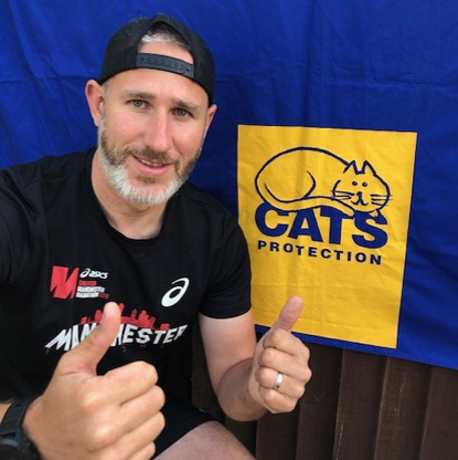 Man in black cap and t-shirt giving thumbs up in front of Cats Protection logo