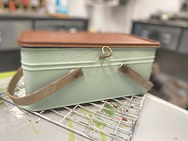 brown painted top and light green painted sides of vintage picnic basket