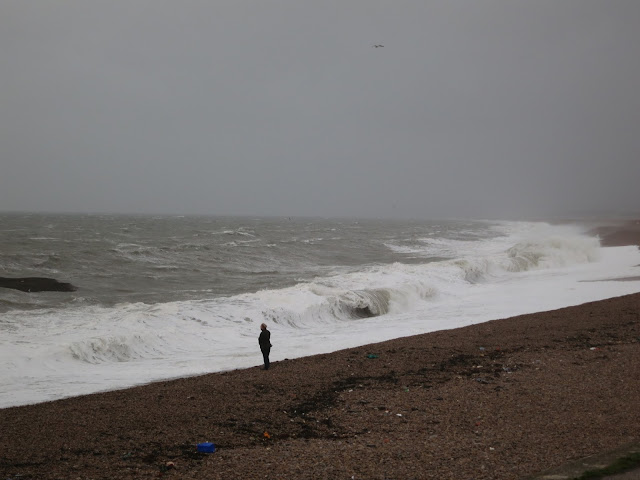Man on Chesil Beach looks out to sea.