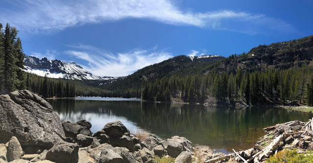 lake in a forest with snowy mountain in background