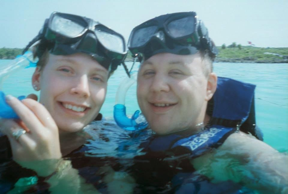 A selfie of my wife and I swimming with snorkel gear on.