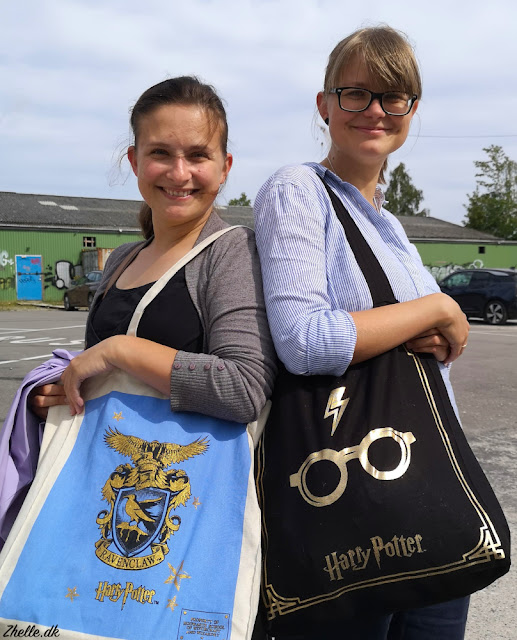 Michelle and Anna showing off shopping bags full of stuff bought at the craft fair. Michelles bag is blue and has a decoration of the Ravenclaw crest, Annas has the Harry Potter symbol with the glasses and the lightning bolt on top