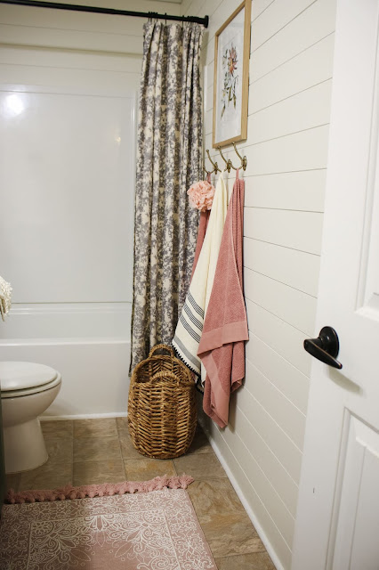 brass towel hooks, art, and a woven basket in a small bathroom