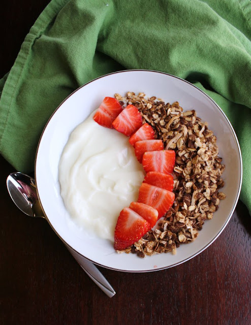 bowl of yogurt topped with chocolate granola and strawberries