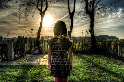 A young girl facing away and looking out to a backyard. There is grass, a picket fence and a bicycle.