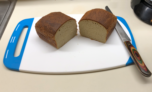 Photo of baked keto bread loaf cut in half on cutting board with bread knife