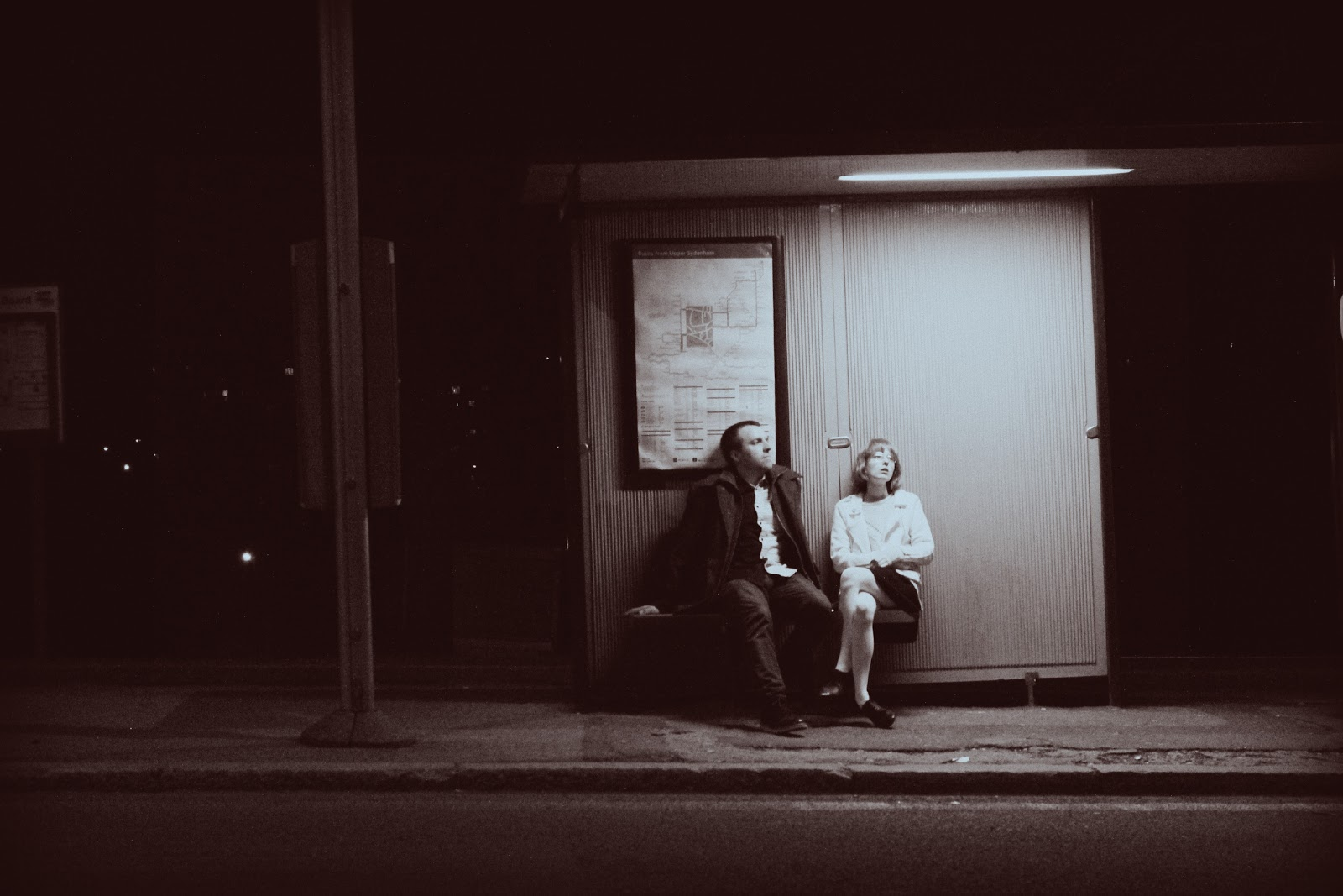 Rescue A Family - A man and woman sit at a bus stop. The scene is deserted and they look bored.