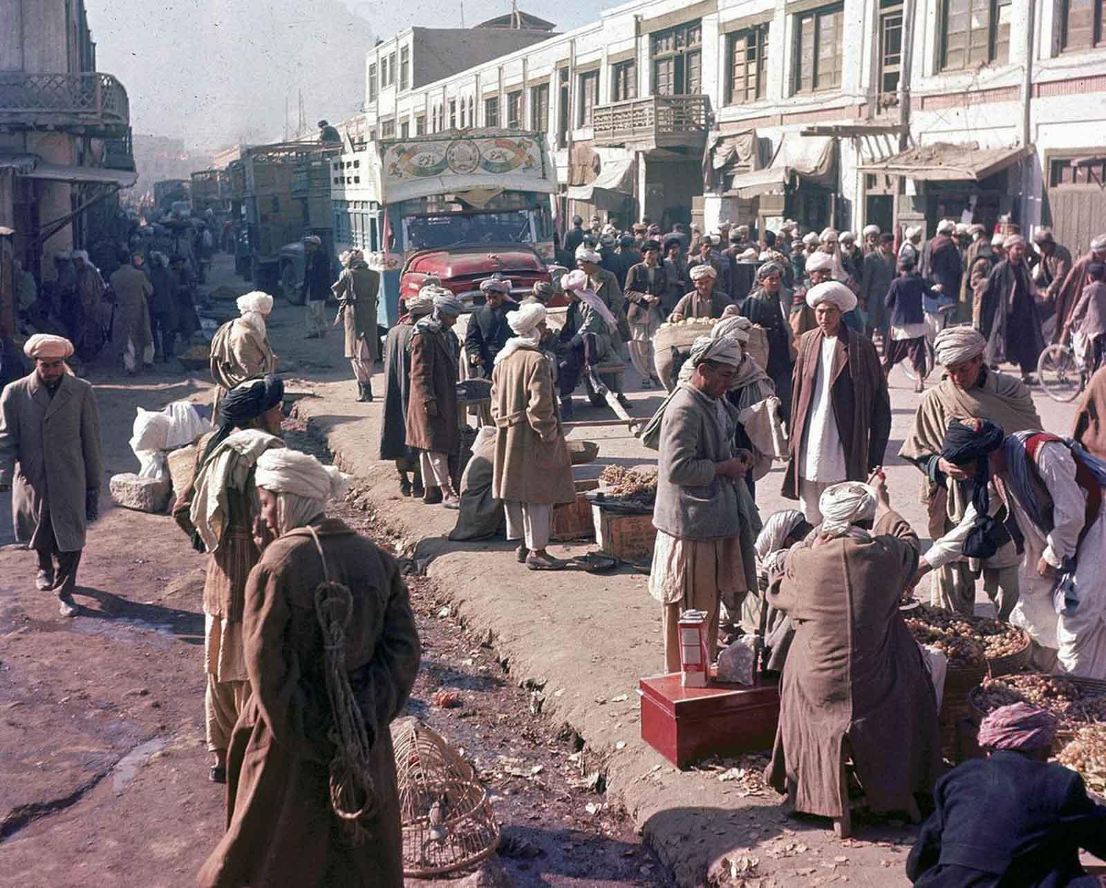 Los hombres pasan por delante de los vendedores de la carretera mientras un camión pintado se abre paso por la concurrida calle de Kabul, Afganistán, en noviembre de 1961.