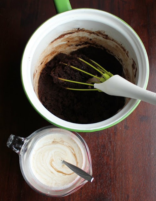 butter and cocoa mixture in saucepan and measuring cup with cream and sour cream mix