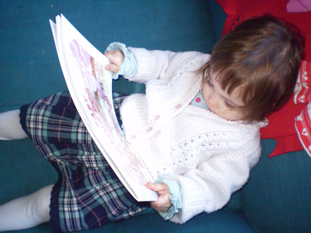Eldest sat on sofa looking at the pages of the book