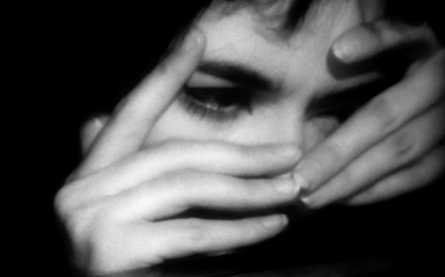 A woman hides her face in her hands