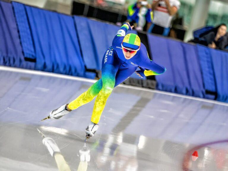 Larissa patina usando um macacão azul e amarelo e óculos de proteção. Ela está semi agachada e com os braços para trás
