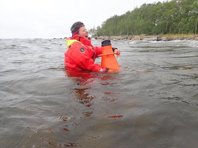 Suvi nauraa vyötäröään myöten meressä seisoessaan pelastautumispuku päällä ja vesikiikarit kädessä.